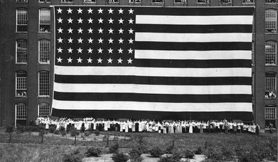 """In this June 29, 1914 photo workers at the Amoskeag Manufacturing Company in Manchester, N.H., pose in front of an American flag they produced to promote the textile mill. The """"Great Flag"""" as it was called later ended up on display at a Chicago department store but hasn't been seen in decades. A replica was displayed at the former mill building on Wednesday, June 14, 2017. (Harlan A. Marshall/Manchester Historic Association via AP)"""