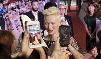 "Actress Tilda Swinton signs autographs for fans during a promotional event for her latest film ""Okja"" in Seoul, South Korea, Tuesday,  June 13, 2017. The film will be released in South Korea on June 29. (AP Photo/Ahn Young-joon)."