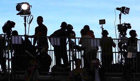 Reporters and photographers on the watch at a press stakeout. Analysts worry about the caustic headlines that often follow. (Associated Press)