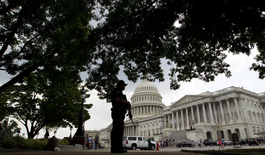 A Capitol Hill Police officer scans the area on Capitol Hill in Washington, Wednesday, June 14, 2017, after House Majority Whip Steve Scalise of La. was shot during during a congressional baseball practice in Alexandria Va. (AP Photo/Jose Luis Magana)