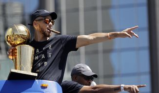 Golden State Warriors' Stephen Curry, top, and his father Dell point to fans during a parade and rally in honor of the Warriors, Thursday, June 15, 2017, in Oakland, Calif., to celebrate the team's NBA basketball championship. (AP Photo/Marcio Jose Sanchez)