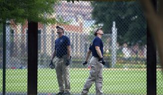 A FBI lab team looks for evidence in the outfield signage at the ball field which is the scene of a multiple shooting in Alexandria, Va., Wednesday, June 14, 2017, after a rifle-wielding attacker opened fire on Republican lawmakers at a congressional baseball practice, wounding House GOP Whip Steve Scalise of Louisiana and several others as congressmen and aides dove for cover. (AP Photo/Cliff Owen)