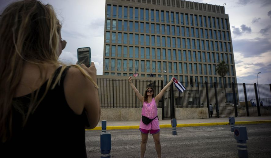 FILE- In this Aug. 11, 2015 file photo, US Citizen Jordan Graddis, 24, left, takes a photo of Emily O'connell, 24, as she holds a US and a Cuban flag in front of the U.S. embassy in Havana, Cuba. On Friday, June 16, 2017, President Donald Trump will give America's Cuba policy its second 180-degree spin in three years. Speaking from Miami, Trump's expected to revive the Cold War goal of starving Cuba's communist system of cash while inciting the population to overthrow it. (AP Photo/Ramon Espinosa, File)