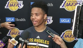 Markelle Fultz, center, speaks with reporters after his private workout with the Los Angeles Lakers at NBA basketball team's training complex Thursday, June 15, 2017, in El Segundo, Calif. The University of Washington guard could be the No. 1 pick in the NBA draft by the Boston Celtics, or he could be available to the Los Angeles Lakers with the second overall pick. (AP Photo/Greg Beacham)
