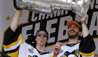 Pittsburgh Penguins goalies Marc-Andre Fleury, left, and Matt Murray hoist the Stanley Cup on stage after riding in the team's NHL hockey Stanley Cup victory parade in Pittsburgh, Wednesday, June 14, 2017. (AP Photo/Gene J. Puskar)