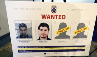 Pictures of people facing criminal charges are seen after a news conference in Washington, Thursday, June 15, 2017, about an May 16, 2017, altercation outside the Turkish Embassy in Washington during the visit of the Turkish president. Police say they've issued arrest warrants for a dozen Turkish security agents and two others accused of taking part in a violent altercation May 16 as Turkey's president visited Washington. (AP Photo/Alex Brandon)