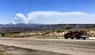 Fire crews head toward the Jemez Mountains along U.S. 550 in Rio Rancho, N.M., as the smoke plume from a prescribed fire grows on Thursday, June 15, 2017. Sandoval County Sheriff's Lt. Keith Elder says deputies were initiating the evacuation of a subdivision along State Highway 4. He was unsure of how many homes were in the area. (Zach Bryan via AP)