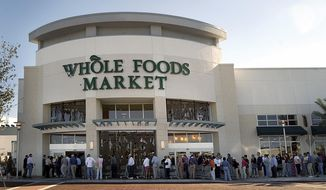 FILE - In this Oct. 26, 2005 file photo, shoppers line up outside a Whole Foods Market before it opens for the day in Palm Beach Gardens, Fla.   Online juggernaut Amazon announced Friday, June 16, 2017, that it is buying Whole Foods in a deal valued at about $13.7 billion, including debt. Amazon.com Inc. will pay $42 per share of Whole Foods Market Inc.  (Cydney Scott/Palm Beach Post via AP)