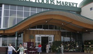 FILE - In this May 9, 2007 file photo, customers are seen outside a Whole Foods Market in Dallas.   Online juggernaut Amazon announced Friday, June 16, 2017, that it is buying Whole Foods in a deal valued at about $13.7 billion, including debt. Amazon.com Inc. will pay $42 per share of Whole Foods Market Inc. AP Photo/LM Otero, file)