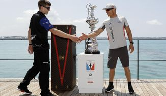 """Peter Burling, helmsman for Emirates Team New Zealand, left, shakes hands with skipper and helmsman Jimmy Spithill for Oracle Team USA, right, in front of the America's Cup trophy, known as the """"Auld Mug,"""" before a news conference Friday, June 16, 2017, in Hamilton, Bermuda. America's Cup match competition begins Saturday. (AP Photo/Gregory Bull)"""
