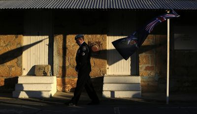 An Australian U.N police officer passes by an Australian Federal Police flag during a flag-lowering ceremony to ended Australia's peacekeeping contribution in Cyprus, inside the U.N buffer zone in divided capital Nicosia, Friday, June 16, 2017. After 53 years of helping to keep the peace on ethnically divided Cyprus, Australia is calling it quits and pulling out its last three police officers serving with a United Nations peacekeeping force. (AP Photo/Petros Karadjias)