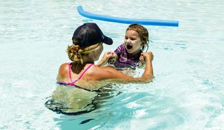 Jennifer Vollmann, 33, plays with her 2-year-old daughter, Izela, in Encanto Pool on Thursday, June 15, 2017 in Phoenix, Ariz. Vollmann, who lives in Phoenix, said her daughter will be back in the pool next week when temperatures are expected to exceed 120 degrees. (AP Photo/Angie Wang)