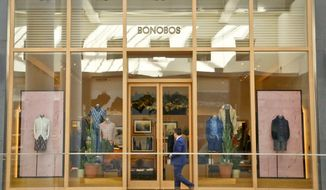 FILE - In this March 20, 2017 file photo, a man walks by the Bonobos Guideshop in New York's Financial District. Walmart says it's buying online men's clothing retailer Bonobos for $310 million in cash, showing that its appetite for hip clothing brands shows no sign of abating as it looks for ways to gain on Amazon. Bonobos, which started out selling pants online, caters to male shoppers looking for help putting together a wardrobe. (AP Photo/Bebeto Matthews)