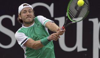 France's Lucas Pouille returns the ball during his semi final match against France's Benoit Paire  at the ATP tennis tournament in Stuttgart, Germany, Saturday, June 17, 2017. (Daniel Maurer/dpa via AP)