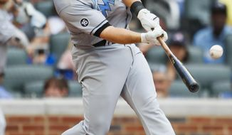 Miami Marlins Tyler Moore hits a two-run home run in the fifth inning of a baseball game against the Atlanta Braves, Saturday, June 17, 2017, in Atlanta. (AP Photo/Todd Kirkland)