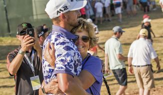 Paula Dougherty of Murrieta, Calif., hugs her son Kevin after he finished the second round of the U.S. open golf tournament Friday, June 16, 2017, at Erin Hills in Erin, Wis. Dougherty finished the day shooting at 1 under par, making the cut. (John Ehlke/West Bend Daily News via AP)