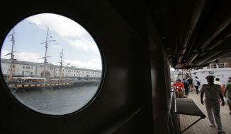 The tall ship Oliver Hazard Perry, top left, is viewed through a porthole on the Peruvian Navy tall ship Union as passers-by, right, walk along a deck aboard the Union during the Sail Boston event, Sunday, June 18, 2017, in Boston. More than 50 tall ships from Europe, South America and the U.S. converged on the city as part of the Rendez-Vous 2017 Tall Ships Regatta. (AP Photo/Steven Senne)