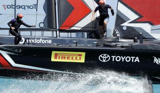 Emirates Team New Zealand skipper Glenn Ashby, left, and cyclist Josh Junior cross the boat as they race Oracle Team USA during the fourth race of America's Cup competition Sunday, June 18, 2017, in Hamilton, Bermuda. (AP Photo/Gregory Bull)