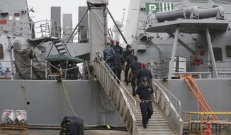 U.S. military personnel work on board the damaged USS Fitzgerald at the U.S. Naval base in Yokosuka, southwest of Tokyo Sunday, June 18, 2017. The search for seven U.S. Navy sailors missing after their destroyer collided with a merchant ship in waters off Japan was called off Sunday after several bodies were found in the ship's flooded compartments, including sleeping quarters.(AP Photo/Eugene Hoshiko)