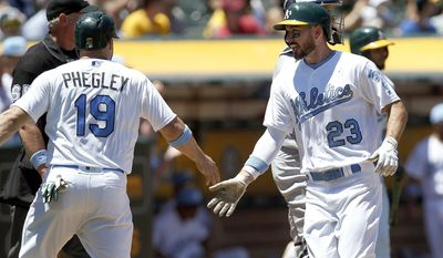 Oakland Athletics' Josh Phegley (19) and Matt Joyce (23) score on a double by Chad Pinder during the third inning of a baseball game against the New York Yankees, Sunday, June 18, 2017, in Oakland, Calif. (AP Photo/Tony Avelar)
