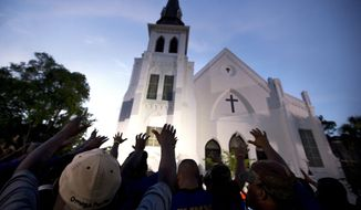 In this June 19, 2015, file photo, the men of Omega Psi Phi Fraternity Inc. lead a crowd of people in prayer outside the Emanuel AME Church, after a memorial for the nine people killed by Dylann Roof in Charleston, S.C.  The pastor of the church is expected to announce the designer of a memorial to the nine people killed in the church's fellowship hall in a racist massacre two years ago Saturday, June 17, 2017. Other ceremonies are also planned to mark the second anniversary of the killings. (AP Photo/Stephen B. Morton, File)