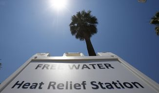 A Salvation Army hydration station sign gets hit by the midday sun as temperatures climb to near-record highs, Monday, June 19, 2017, in Phoenix. (AP Photo/Ross D. Franklin)
