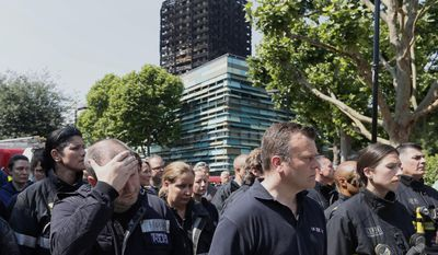 Emergency services workers take part in a minute's silence in front of Grenfell Tower in London, Monday, June 19, 2017. Tens of people died when a fire engulfed the high-rise apartment block in west London last week.(AP Photo/Kirsty Wigglesworth)