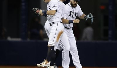 Tampa Bay Rays, from left, Corey Dickerson, Peter Bourjos, and Steven Souza Jr., celebrate the team's 6-5 win over the Cincinnati Reds in a baseball game Tuesday, June 20, 2017, in St. Petersburg, Fla. (AP Photo/Chris O'Meara)