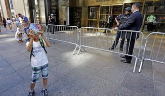 Tourists take photos outside Trump Tower, in New York, Tuesday, June 20, 2017. The security cordon that New York City police put up around Trump Tower after the election has loosened up in recent days and some neighborhood merchants are breathing a big sigh of relief. The security barriers and checkpoints, which were relaxed after Melania and Barron Trump decamped for the White House, had hindered foot traffic and made getting to some businesses difficult. (AP Photo/Richard Drew)
