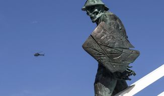 A helicopter flies past the Spartacus statue at the Spartak Stadium in Moscow, Russia, Tuesday, June 20, 2017. The 25-meter high monument, a metal gladiator atop a vast soccer ball, towers outside Moscow's Spartak stadium, one of Russia's Confederations Cup stadiums. (AP Photo/Denis Tyrin)
