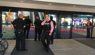 Police officers gather at a terminal at Bishop International Airport, Wednesday morning, June 21, 2017, in Flint, Mich. Officials evacuated the airport Wednesday, where a witness said he saw an officer bleeding from his neck and a knife nearby on the ground.  On Twitter, Michigan State Police say the officer is in critical condition and the FBI was leading the investigation. (Dominic Adams/The Flint Journal-MLive.com via AP)