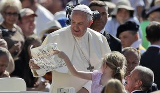 Pope Francis is presented with a drawing by a child as he arrives for his weekly general audience in St. Peter's Square at the Vatican, Wednesday, June 21, 2017. (AP Photo/Alessandra Tarantino)