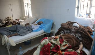 FILE - In this Monday, May 15, 2017 file photo, people are treated for suspected cholera infection at a hospital in Sanaa, Yemen. The U.N. health agency and some major partners have agreed on Wednesday, June 21, 2017 to send 1 million doses of cholera vaccine to Yemen to help stanch a spiraling and increasingly deadly caseload in the impoverished country, which is already facing war and the risk of famine. (AP Photo/Hani Mohammed, file)