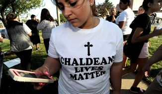 Astevana Shaya, 28, of Sterling Heights, Mich., wears a Chaldeans Lives Matter T-shirt at the protest, Monday, June 12, 2017 in Sterling Heights, Mich.  The arrests of dozens of Iraqi Christians in southeastern Michigan by U.S. immigration officials appear to be among the first roundups of people from Iraq who have long faced deportation, underscoring rising concerns in other immigrant communities.  (Todd McInturf/Detroit News via AP)  /Detroit News via AP)