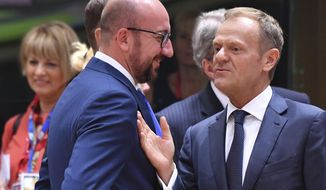 European Council President Donald Tusk, right, speaks with Belgian Prime Minister Charles Michel during a round table meeting at an EU summit in Brussels on Thursday, June 22, 2017. European Union leaders are gathering for a two day summit to weigh measures in which to tackle terrorism and migration and to create closer defense ties. (AP Photo/Geert Vanden Wijngaert)