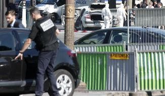 Scientific police officers investigate on the suspected car, center rear, after a man rammed into a police convoy on the Champs Elysees avenue in Paris, Monday, June 19, 2017. France's interior minister says the attempted attack on security forces on the Champs-Elysees shows the threat is still very high in the country and justifies the state of emergency. (AP Photo/Thibault Camus)