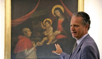"Former director of the Vatican Museums Francesco Buranelli speaks in front of a copy by Pietro Facchetti of Renaissance master Pintoricchio's mural panting depicting Borgia Pope Alexander VI on his knees before Baby Jesus held by the Virgin Mary that was decorating a private chamber in the Borgia papal apartment at the Vatican, part of the exhibition ""Pintoricchio. Painter of the Borgias. The mistery of Giulia Farnese revealed."" on display at the Capitoline Museums in Rome, Thursday, June 22, 2017. (AP Photo/Domenico Stinellis)"