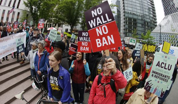 FILE--In this May 15, 2017, file photo, protesters wave signs and chant during a demonstration against President Donald Trump's revised travel ban outside a federal courthouse in Seattle. A federal judge said Wednesday, June 21, 2017, that a class-action lawsuit challenging a once-secret government program that delayed immigration and citizenship applications by Muslims can move forward. (AP Photo/Ted S. Warren, file)