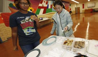 In this Jan. 27, 2017 photo, Thandi Glick looks on as the foreign exchange student that her family is hosting, Miaofan Chen, begins her way through the serving line during a potluck meal for Chinese exchange students and their families at a school in Denver. For many American families, hosting a foreign student is a way to bring other cultures to their doorsteps without ever leaving home. (AP Photo/David Zalubowski)