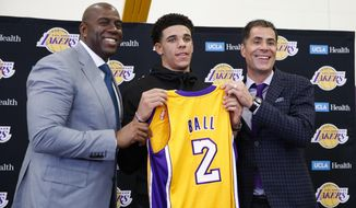 Los Angeles Lakers' Lonzo Ball, center, poses for photos with Magic Johnson, left, and general manager Rob Pelinka during a news conference, Friday, June 23, 2017, in El Segundo, Calif. (AP Photo/Jae C. Hong)