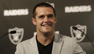 Oakland Raiders quarterback Derek Carr smiles while speaking at a news conference in Oakland, Calif., Friday, June 23, 2017. Carr finalized a five-year contract extension that will keep him with the team through the 2022 season. (AP Photo/Jeff Chiu)