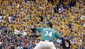 """Fans hold """"K"""" cards, designating a strikeout, as Seattle Mariners starting pitcher Felix Hernandez throws against the Houston Astros during the second inning of a baseball game Friday, June 23, 2017, in Seattle. (AP Photo/Elaine Thompson)"""