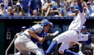Kansas City Royals' Alcides Escobar beats the tag by Toronto Blue Jays catcher Luke Maile to score on a sacrifice fly hit by Whit Merrifield during the third inning of a baseball game Saturday, June 24, 2017, in Kansas City, Mo. (AP Photo/Charlie Riedel)