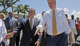 New York City Mayor Bill de Blasio, right, and Miami Beach Mayor Philip Levine, left, talk during a tour where the city has raised streets and installed pumps to combat rising tides, Friday, June 23, 2017, in Miami Beach, Fla. The U.S. Conference of Mayors opens its annual meeting Friday in Miami Beach. Mayors of cities with populations of 30,000 or more will discuss plans to reduce the nation's carbon footprint and protect immigrant families. (AP Photo/Alan Diaz)
