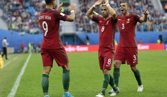 Portugal's Andre Silva, left, celebrates with teammates Joao Moutinho and Pepe after scoring his side's third goal during the Confederations Cup, Group A soccer match between New Zealand and Portugal, at the St. Petersburg Stadium, Russia, Saturday, June 24, 2017. (AP Photo/Ivan Sekretarev)