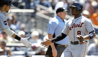 Detroit Tigers' Justin Upton, right, gets congratulations from Nicholas Castellanos after scoring on a triple by Mikie Mahtook during the fourth inning of a baseball game against the San Diego Padres in San Diego, Sunday, June 25, 2017. (AP Photo/Alex Gallardo)