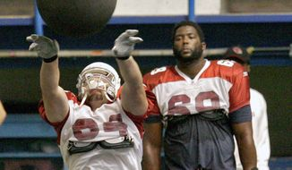 Arizona Cardinals center Scott Peters, front, throws a weighted ball as teammate Mike Gandy looks on during their NFL football training camp Saturday, July 26, 2008, in Flagstaff, Ariz. (AP Photo/Matt York)