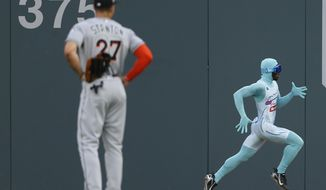 """Atlanta Braves grounds crew member and former college track star Nigel Talton runs past Miami Marlins right fielder Giancarlo Stanton (27) as he races a fan from the left field corner to the right field corner during Atlanta Braves """"Beat The Freeze"""" promotion during a baseball game against the Miami Marlins Friday, June 16, 2017, in Atlanta. (AP Photo/John Bazemore)"""