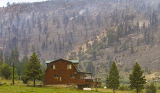 This Saturday, June 24, 2017, photo, shows a cabin near Panguitch Lake near Panguitch, Utah., that was not burned by a wildfire. Nearly 1,000 firefighters battled a Utah wildfire that grew Sunday morning that has prompted the evacuation of over a 1,000 people from hundreds of homes and cabins. (Jordan Allred/The Spectrum via AP)