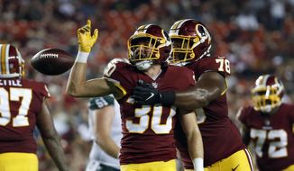 Washington Redskins defensive back Troy Apke (30) celebrates his interception with defensive tackle Ondre Pipkins (78) during the first half of a preseason NFL football game against the New York Jets, Thursday, Aug. 16, 2018, in Landover, Md. (AP Photo/Alex Brandon) **FILE**